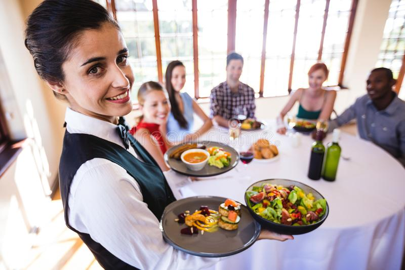Waitress holding food on plate in restaurant stock images