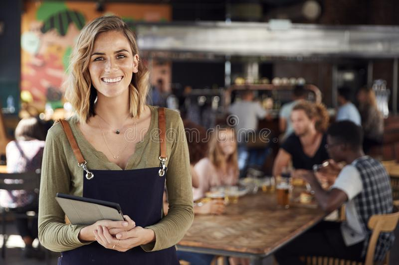 Portrait Of Waitress Holding Menus Serving In Busy Bar Restaurant stock photos