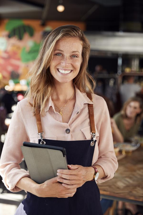 Portrait Of Waitress Holding Menus Serving In Busy Bar Restaurant stock image