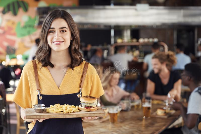 Portrait Of Waitress Serving Food To Customers In Busy Bar Restaurant royalty free stock photography