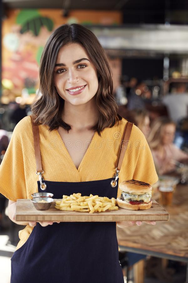 Portrait Of Waitress Serving Food To Customers In Busy Bar Restaurant stock photography