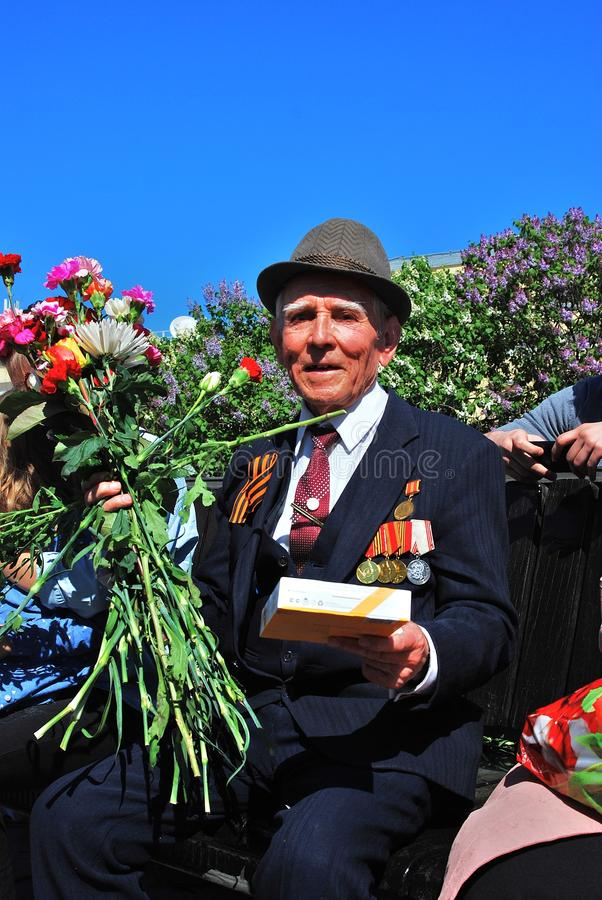 Portrait of a war veteran holding flowers and looking at camera. MOSCOW - MAY 09, 2014: Portrait of a war veteran holding flowers and looking at camera. Victory stock photos