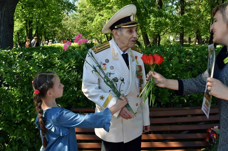 Portrait of war veteran receiving flowers. Victory Day celebration in Gorky park in Moscow. Date: May 09, 2018. Color photo stock image