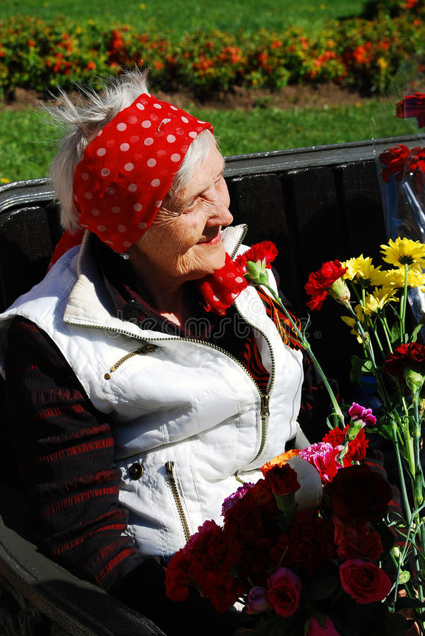 Portrait of a war veteran woman sitting on a bench smiling. MOSCOW - MAY 09, 2014: Portrait of a war veteran woman sitting on a bench smiling. Victory Day royalty free stock images