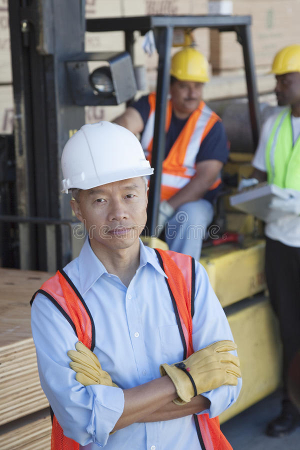 Portrait of warehouse manager with arms crossed and colleagues in background royalty free stock image