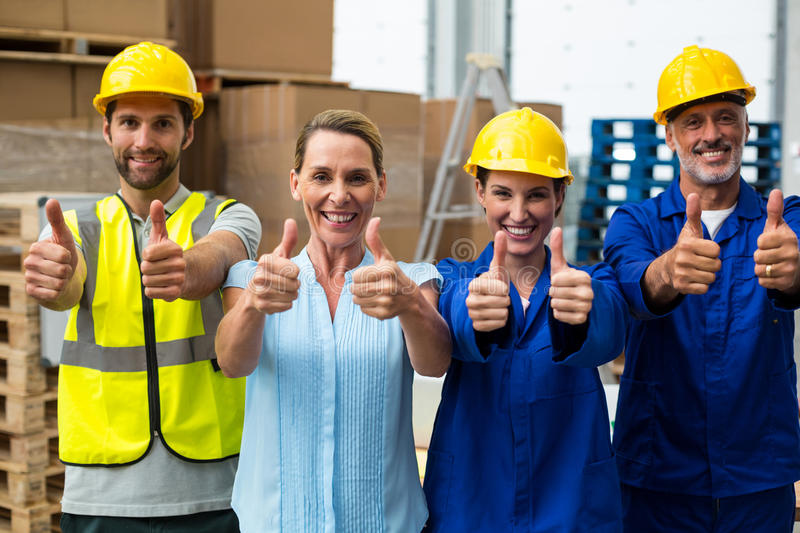 Portrait of warehouse manager and worker showing thumbs up. In warehouse stock photography