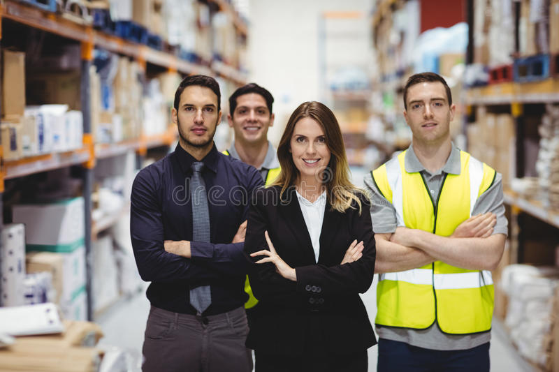 Portrait of warehouse manager and workers. In warehouse stock photos
