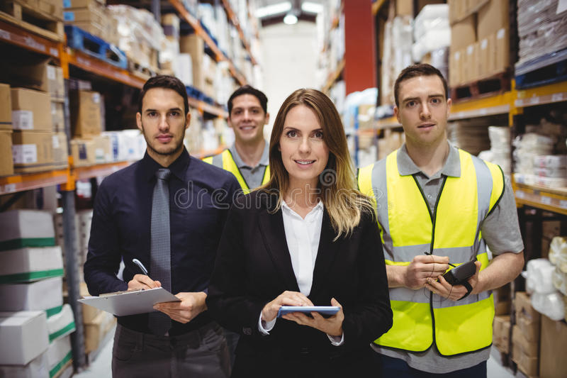 Portrait of warehouse manager and workers. In warehouse royalty free stock image
