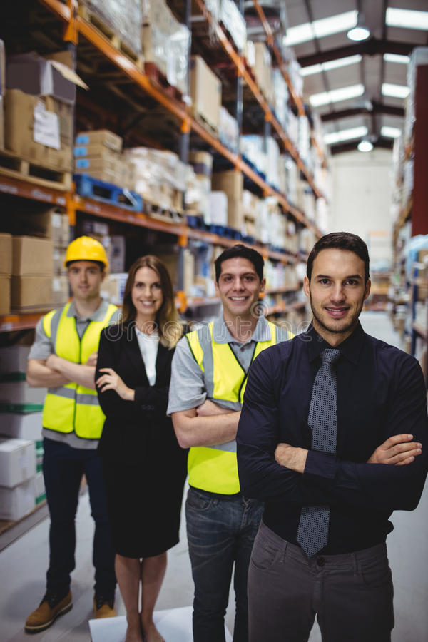 Portrait of warehouse manager and workers. In warehouse stock photography