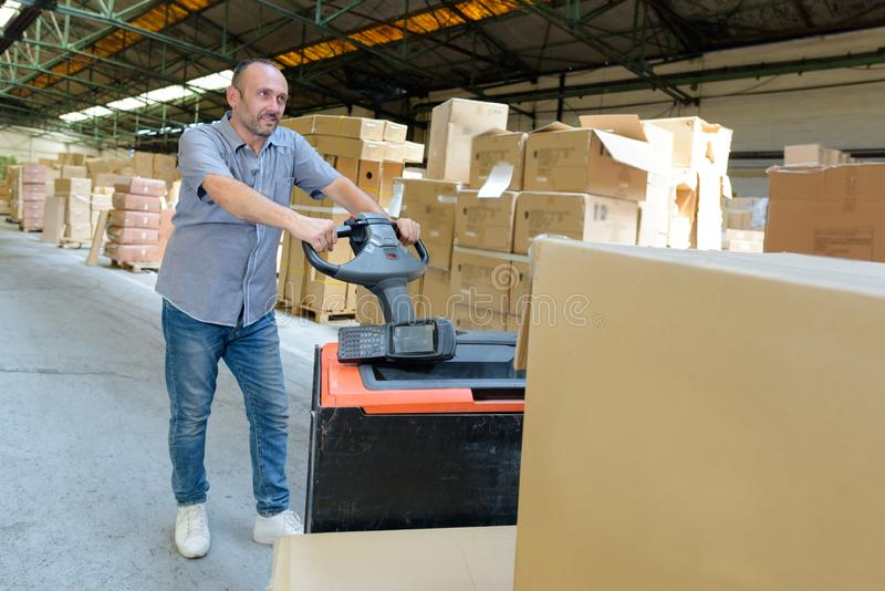 Portrait warehouse worker carrying boxes. Portrait of a warehouse worker carrying boxes royalty free stock photography