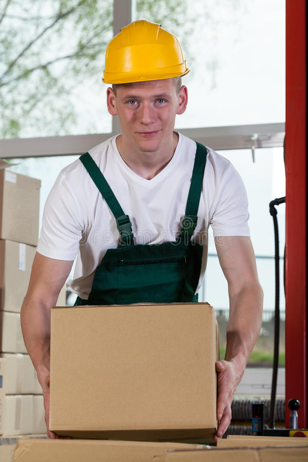 Portrait of a warehouse worker lifting a box royalty free stock photography
