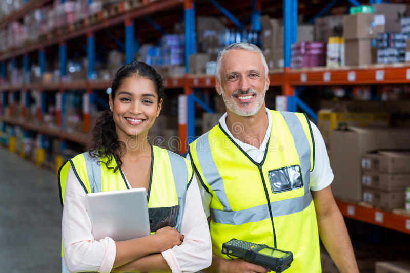 Portrait of warehouse workers standing with digital tablet and barcode scanner royalty free stock photography
