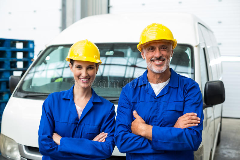Portrait of warehouse workers standing together with arms crossed royalty free stock photography