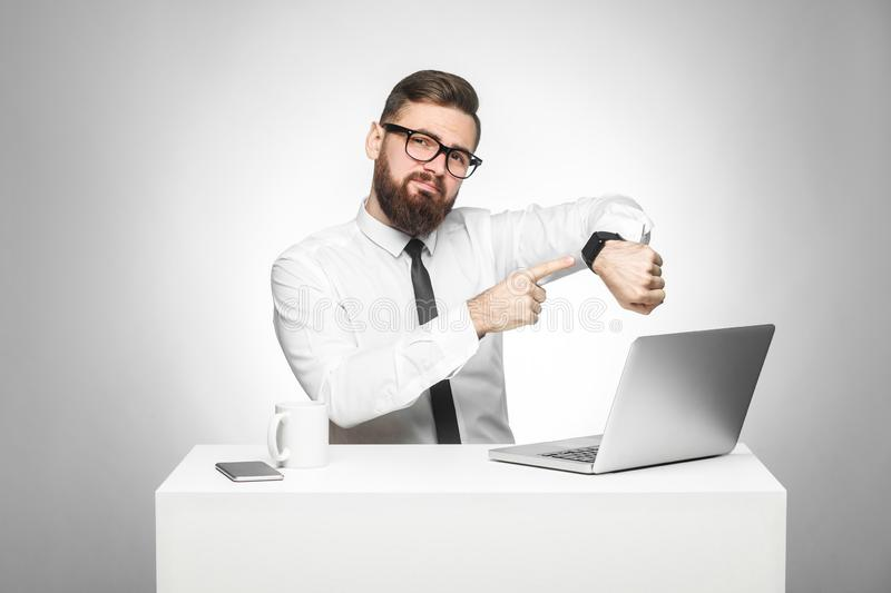 Portrait of warning handsome bearded young boss in white shirt and black tie are sitting in office and pointing finger to him hand royalty free stock photo