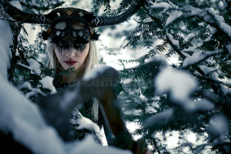 Portrait of warrior woman in image of viking with horned helmet hidden among branches of trees. Portrait of beautiful warrior woman in image of viking with royalty free stock photo
