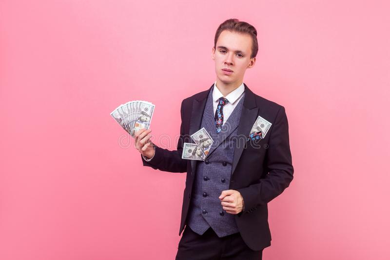 Portrait of wealthy rich man holding money and looking arrogant successful. indoor studio shot isolated on pink background. Portrait of wealthy rich man in royalty free stock photo