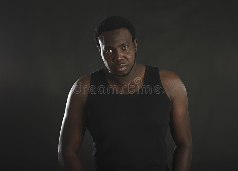Portrait of well-built African-American man standing on black isolated background. stock photography