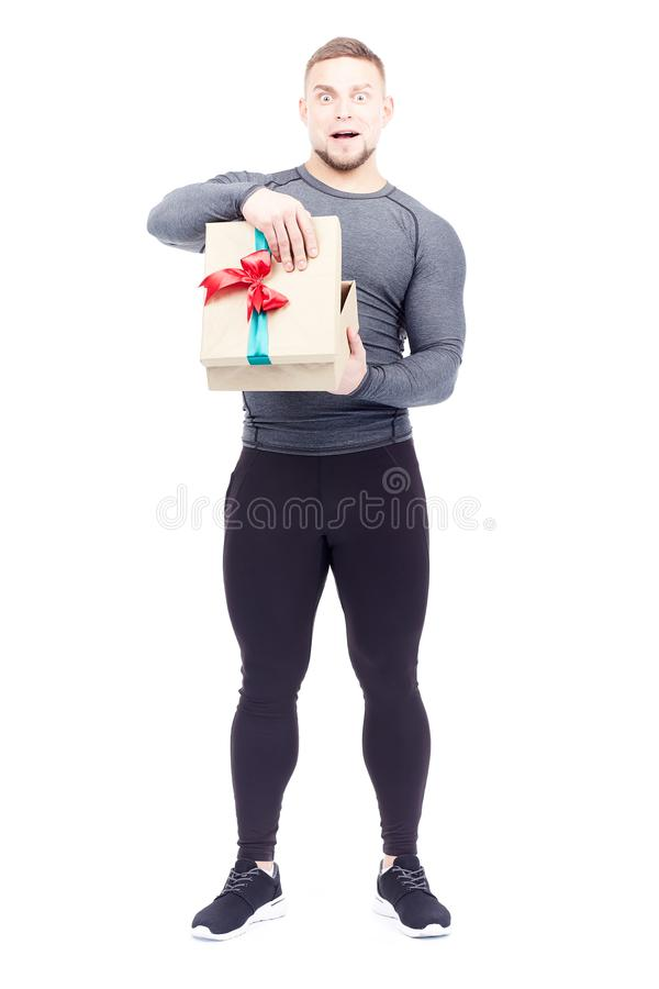 Athlete holding gift box. Portrait of well-muscled athlete posing with gift box on white background royalty free stock photography