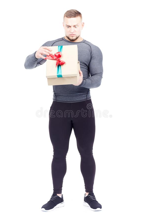 Athlete holding gift box. Portrait of well-muscled athlete posing with gift box on white background stock photos