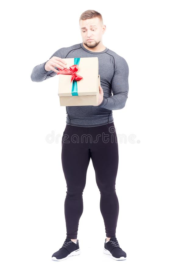 Athlete holding gift box. Portrait of well-muscled athlete posing with gift box on white background stock images