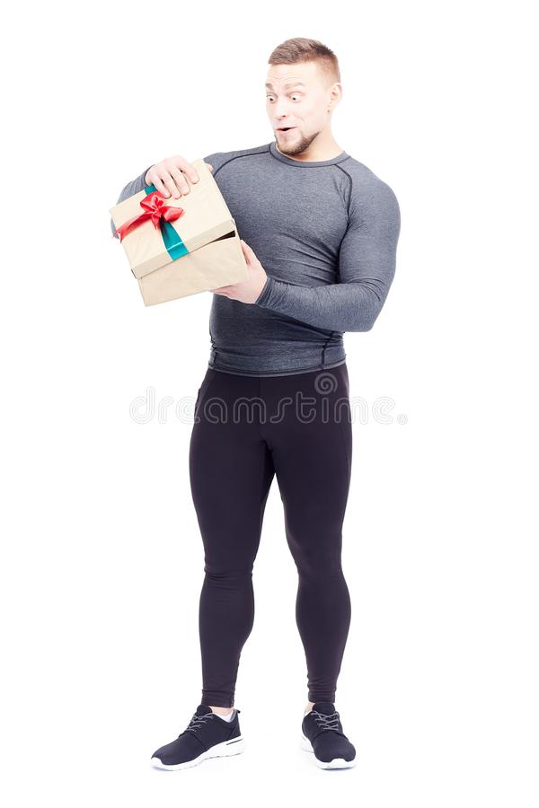 Athlete holding gift box. Portrait of well-muscled athlete posing with gift box on white background stock image