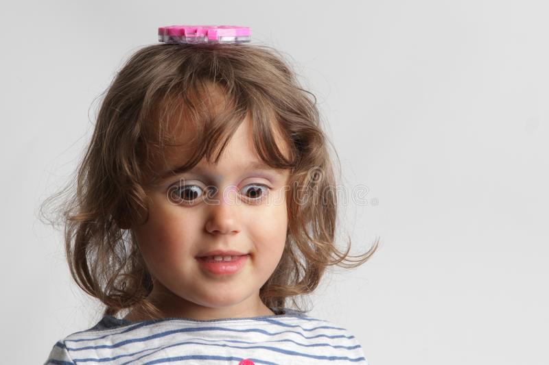 Portrait on white background of a 3-4 year old girl playing royalty free stock image