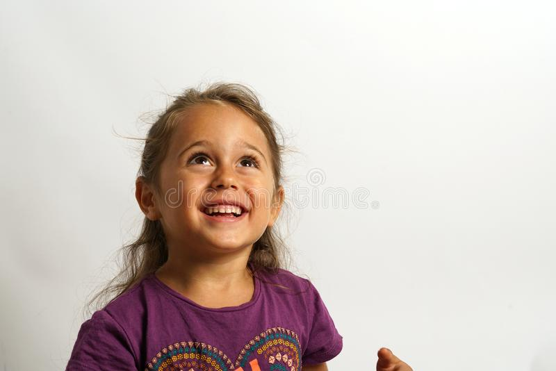 Portrait on white background of a 4 year old Italian girl looking up. Smiling, sweet, floor, pretty, cute, european, child, caucasian, cheerful, female stock image