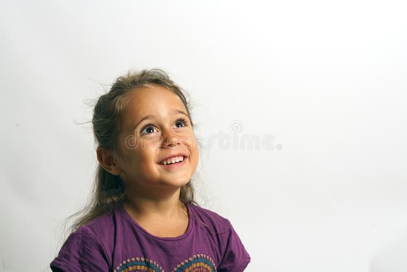 Portrait on white background of a 4 year old Italian girl looking up. Smiling, sweet, floor, pretty, cute, european, child, caucasian, cheerful, female royalty free stock images