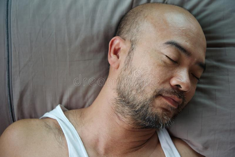 Portrait of bald beard Japanese sleeping man on grey pillow royalty free stock image