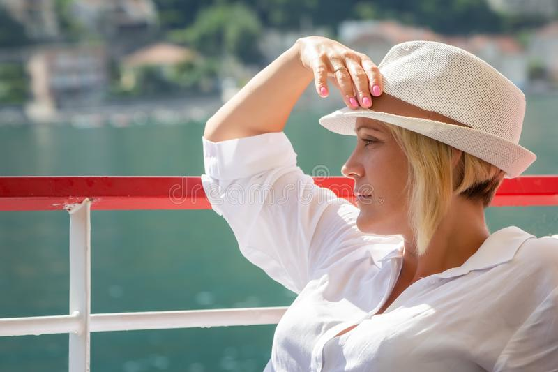 Portrait of a white blond girl in a hat on the background of the turquoise sea royalty free stock photography