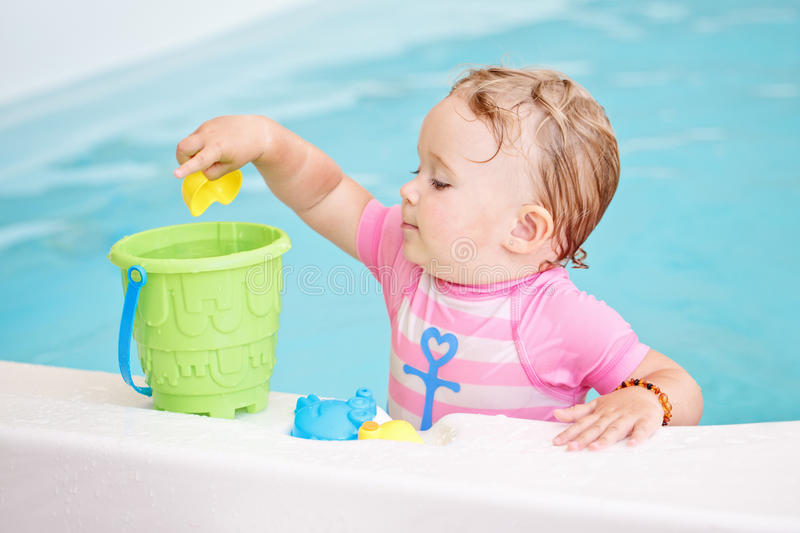 Portrait of white Caucasian baby girl playing with toys in water on swimming pool nosing inside. Looking away, training to swim, healthy active lifestyle stock images