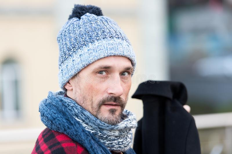 Portrait of man in winter knitted hat and scarf. white guy on street hold black coat. Close up of bearded man in hat royalty free stock photo