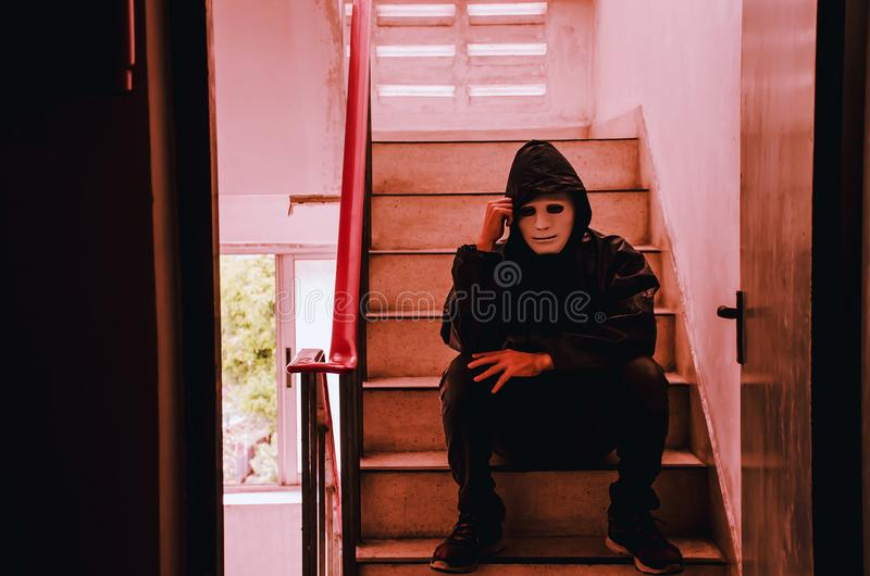 Portrait of white mask and hoodie sitting on old stairs. Selective focus on hands. Sadness, despair, dark, concept stock image
