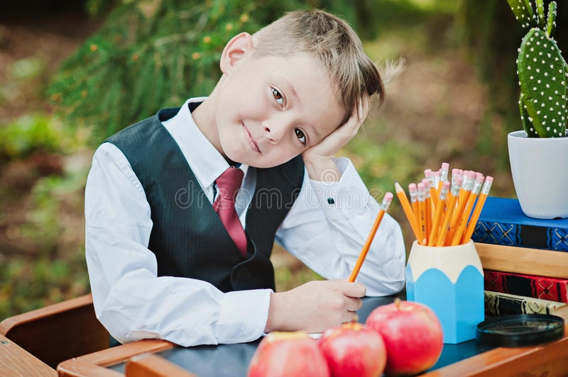 Portrait of a wistful first-grader boy sitting at a desk royalty free stock photography