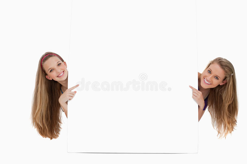 Portrait of wo long hair women back of a blank sign. Portrait of two long hair women back of a blank sign against white background stock images