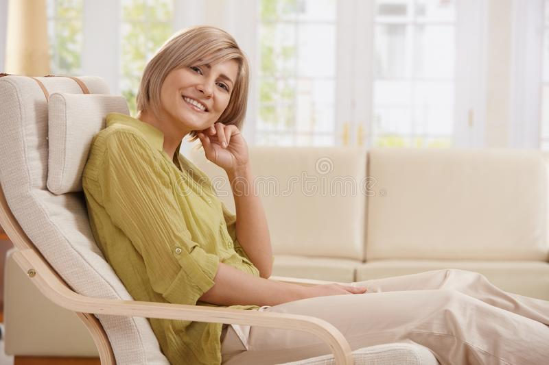Portrait of woman in armchair. Portrait of mid-adult woman smiling at camera sitting in armchair in bright living room with hand up at face royalty free stock images