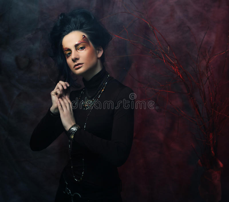 Portrait of woman with artistic make-up in blue smoke, party the stock photos