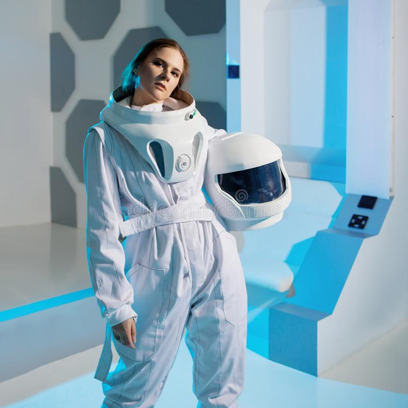 Portrait of a woman astronaut in a space suit, dreamy look up. Futuristic astronaut on Board the spacecraft. Portrait of a woman astronaut in a space suit royalty free stock photography