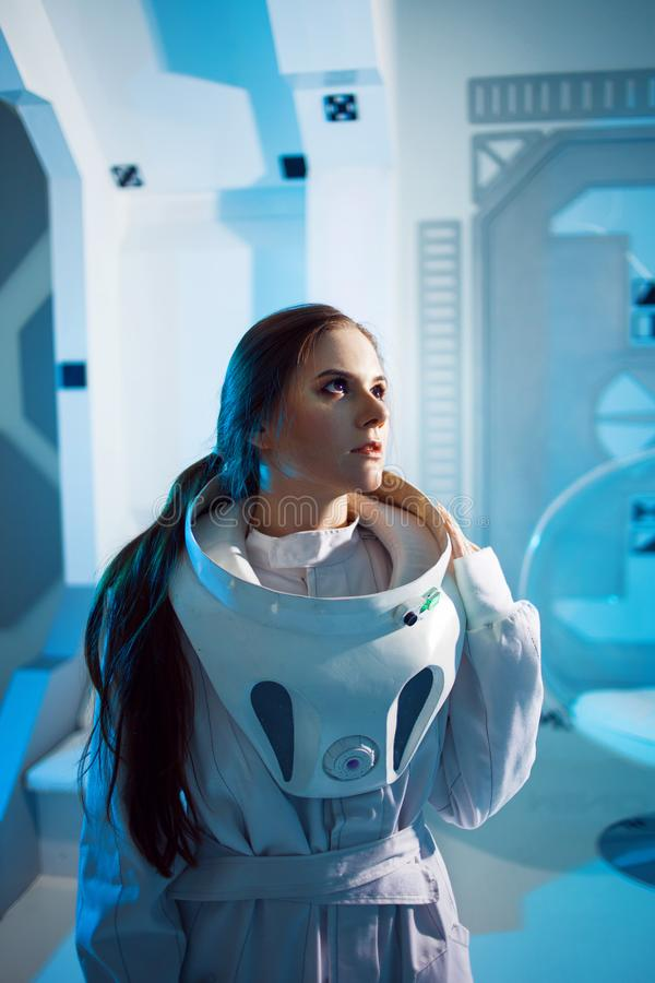 Portrait of a woman astronaut in a space suit, dreamy look up. Futuristic astronaut on Board the spacecraft. Portrait of a woman astronaut in a space suit royalty free stock photos