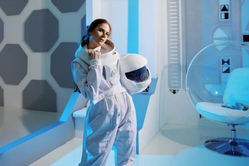 Portrait of a woman astronaut in a space suit, dreamy look up. Futuristic astronaut on Board the spacecraft. Portrait of a woman astronaut in a space suit royalty free stock photo
