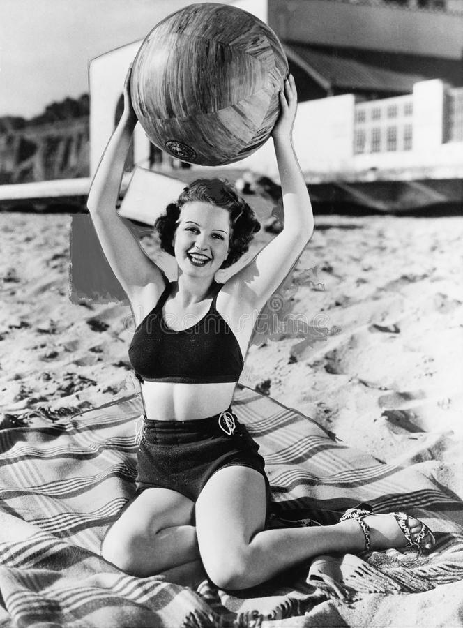 Portrait of woman with ball at beach. (All persons depicted are no longer living and no estate exists. Supplier grants that there will be no model release royalty free stock photo