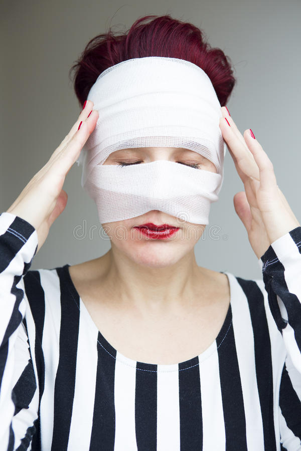 Portrait of woman with bandages wrapped around her head. Portrait of beautiful red haired woman with bandages wrapped around her head royalty free stock photos