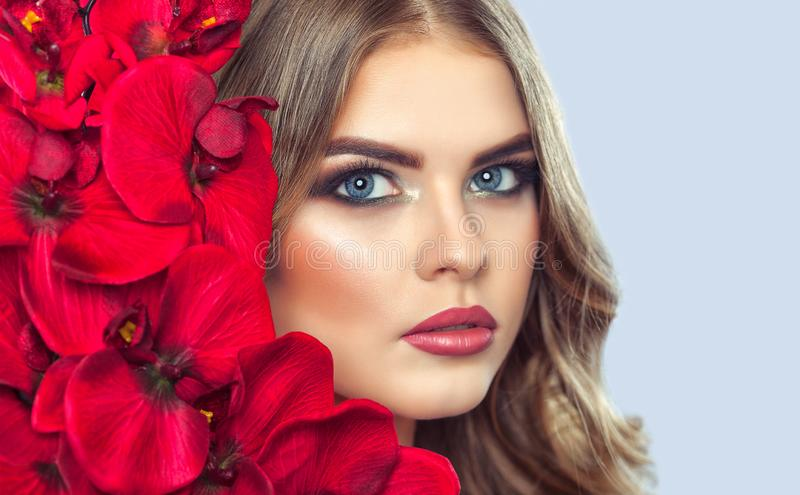 Portrait of a woman with beautiful make-up holds a red orchid in his hands royalty free stock photo