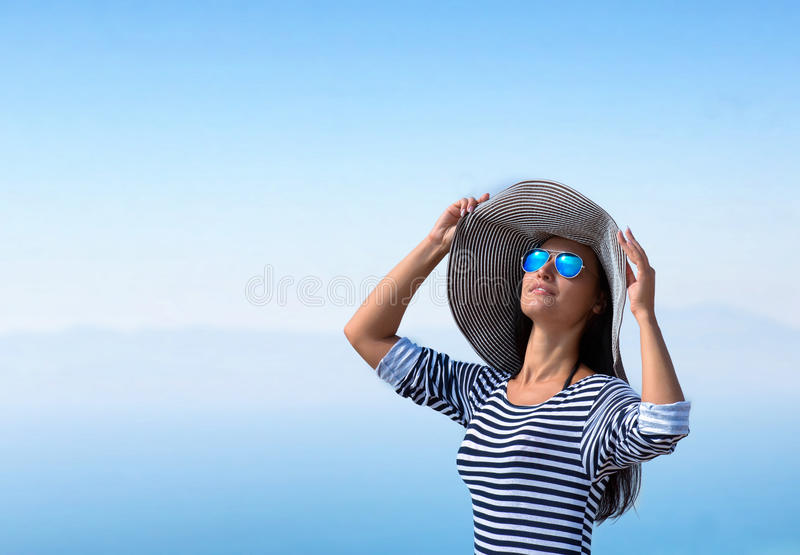 Portrait of a woman in the big stripy hat. Portrait of a beautiful woman in the big stripy hat and sunglasses looking up against a sea stock images