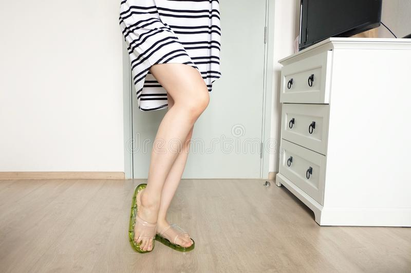 Portrait of Woman in Black and White Stripes Pajamas Dress. Green Flip-Flops Sandals. Beautiful Female Standing at Wh stock images