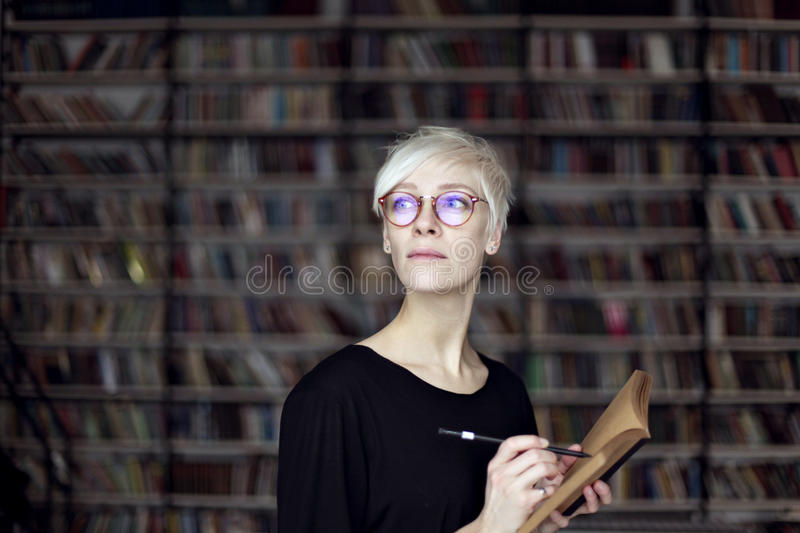 Portrait of woman with blonde hair and eyeglasses in a library, opened book. Hipster student. Education concept.  stock photo