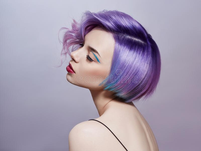 Portrait of a woman with bright colored flying hair, all shades of purple. Hair coloring, beautiful lips and makeup. Hair stock image