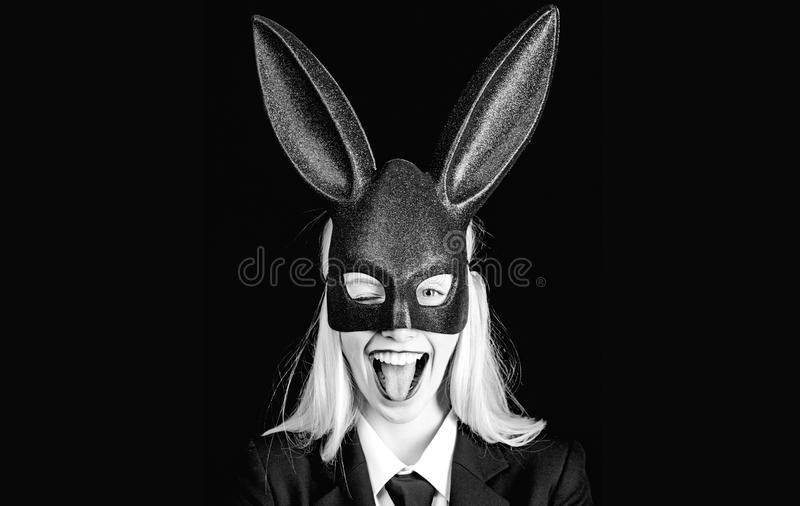 Portrait of a woman in bunny ears winking. Closeup of winking bunny girl face - girl winking and tongue out. Portrait of a woman in bunny ears winking. Closeup royalty free stock image