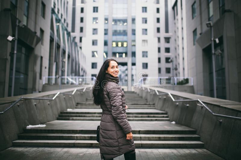 Portrait of a woman on a business theme. Young Caucasian brunette girl in long jacket, coat with black leather bag stands on busin stock photo