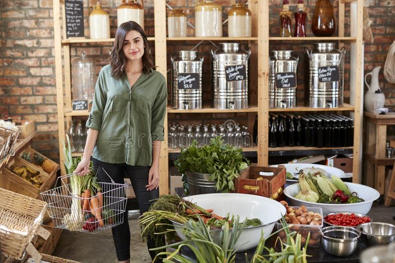 Portrait Of Woman Buying Fresh Fruit And Vegetables In Sustainable Plastic Free Grocery Store stock photography